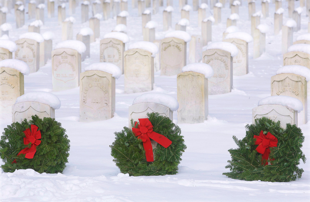 . Falling snow rest on the headstones of war veterans at Camp Butler National Cemetery Tuesday, Dec. 17, 2013, in Springfield, Ill. Cold winter weather stays locked in the Midwest and a forecast of more snow for the Northeast. Camp Butler National Cemetery was one of hundreds of cemeteries across the country participating in Wreaths Across America, placing holiday wreaths to honor the nation�s veterans. (AP Photo/Seth Perlman)
