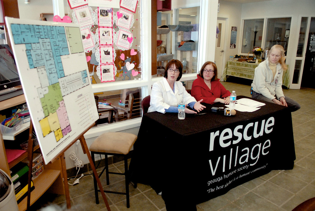 . Jeff Forman/JForman@News-Herald.com Rescue Village medical director Megan Volpe, left, shows the plans for the shelter\'s expansion during a press conference Feb. 26 at the shelter. With her are Hope Brustein, executive director, and Jane Geisse, a volunteer.
