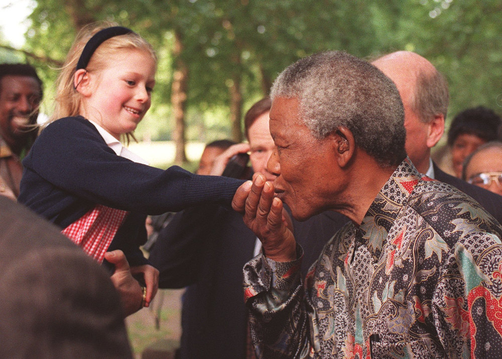 Description of . South African President Nelson Mandela kisses the hand of an unidentified girl during an early morning stroll in London's St. James' Park Wednesday, July 10, 1996. President Mandela is on a four-day State visit to Britain. (AP Photo/Andrew Buurman)