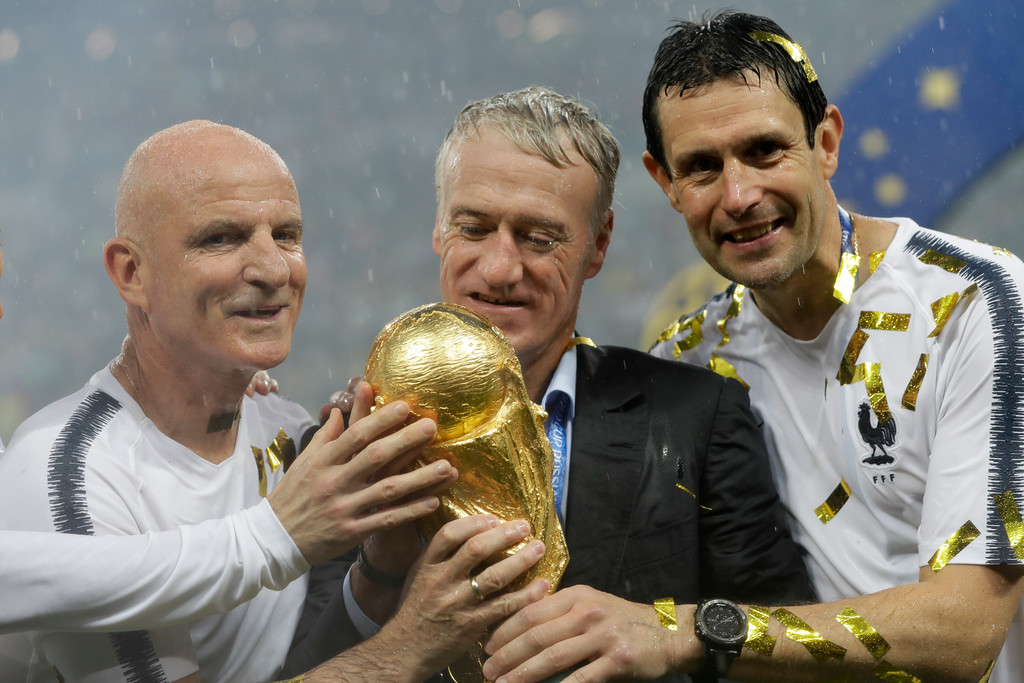 . France head coach Didier Deschamps, second right, holds the trophy at the end of the final match between France and Croatia at the 2018 soccer World Cup in the Luzhniki Stadium in Moscow, Russia, Sunday, July 15, 2018. (AP Photo/Matthias Schrader)