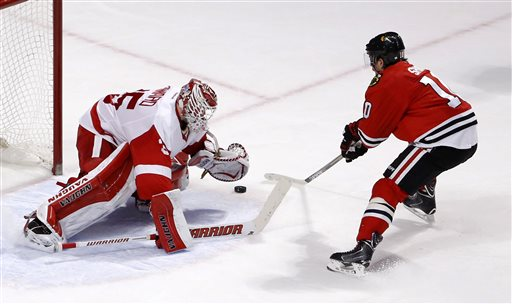 . Detroit Red Wings goalie Jimmy Howard (35) makes a save on a shot by Chicago Blackhawks left wing Patrick Sharp (10) giving the Red Wings\' a 3-2 win during a shootout period of an NHL hockey game Wednesday, Feb. 18, 2015, in Chicago. (AP Photo/Charles Rex Arbogast)