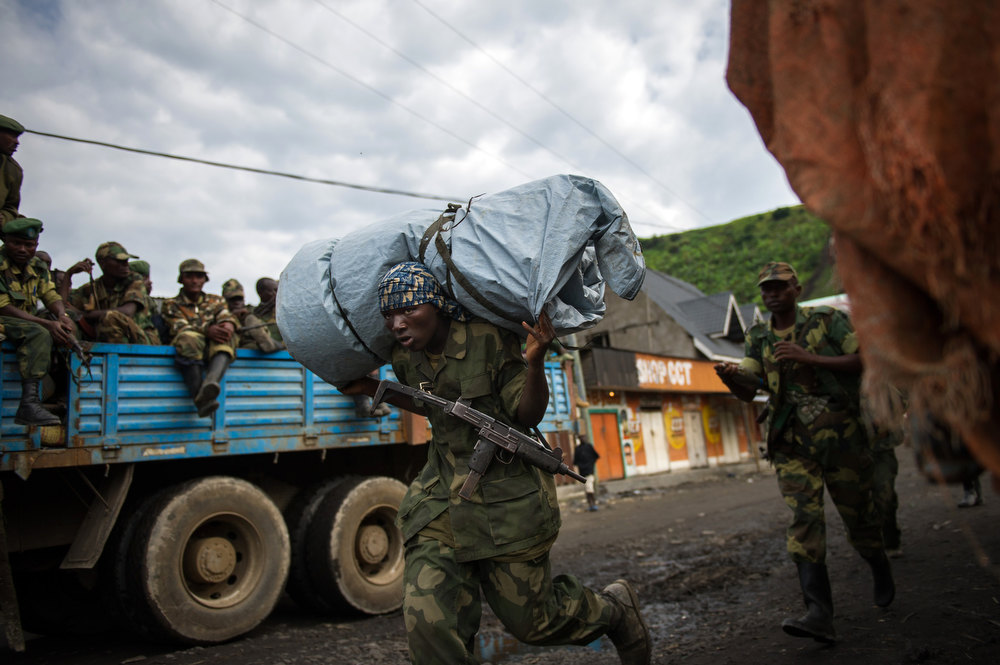 Description of . An M23 reebl carries equipment through Sake having left his base in the hills north of the town in the east of the Democratic Republic of the Congo on November 30, 2012. Hundreds of Congolese rebels withdrew on November 30 from frontline positions around Goma as promised under a regionally brokered deal, while police entered the key eastern city to take over control.  PHIL MOORE/AFP/Getty Images