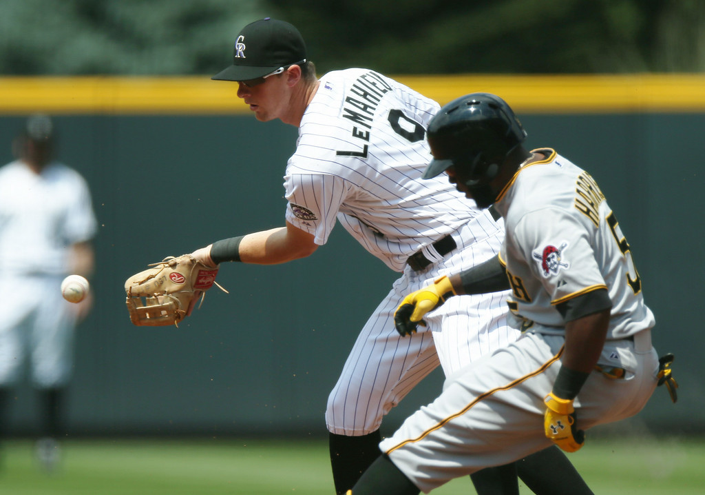. Colorado Rockies second baseman DJ LeMahieu, back, fields throw as Pittsburgh Pirates\' Josh Harrison pulls into second base with a double in the first inning of a baseball game in Denver on Sunday, July 27, 2014. (AP Photo/David Zalubowski)
