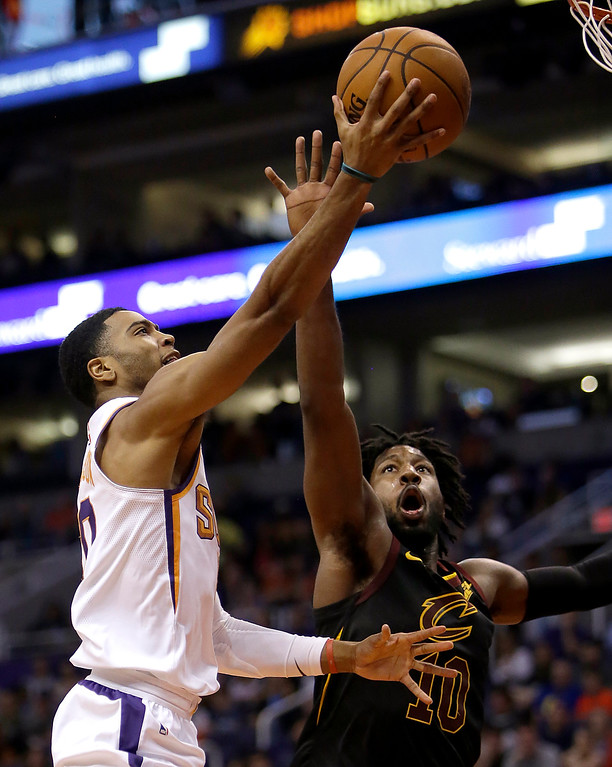 . Phoenix Suns guard Troy Daniels (30) shoots over Cleveland Cavaliers guard John Holland in the second half during an NBA basketball game, Tuesday, March 13, 2018, in Phoenix. The Cavaliers defeated the Suns 129-107. (AP Photo/Rick Scuteri)
