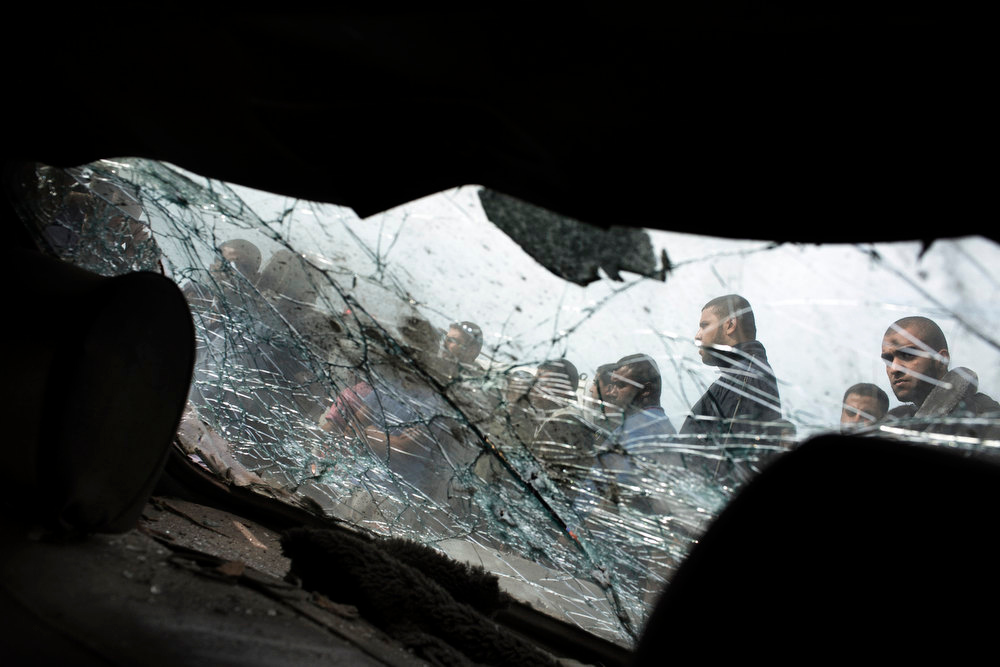 Description of . Palestinians are seen through the shattered windshield of a car as they inspect the site of an Israeli airstrike on the Shati refugee camp in Gaza City on November 18, 2012. Two people were killed, one of them a child, when an Israeli missile hit a beachfront refugee camp in Gaza City, the Hamas-run health ministry and witnesses said. MARCO LONGARI/AFP/Getty Images