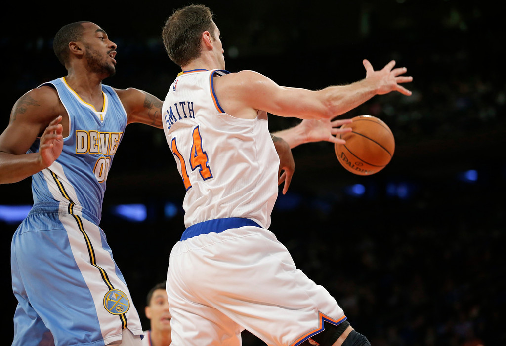 . Denver Nuggets forward Darrell Arthur (00) knocks the ball from the hands of New York Knicks center Jason Smith (14) in the first half of an NBA basketball game in New York, Sunday, Nov. 16, 2014. The Knicks defeated the Nuggets 109-93. (AP Photo/Kathy Willens)