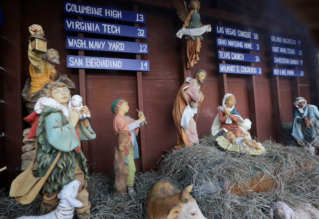 . A traditional Nativity scene depicts the birth of Jesus, Thursday, Dec. 7, 2017, in front of St. Susanna\'s Catholic Parish, in Dedham, Mass., but also includes signs listing U.S. mass shootings and the number of people killed at each. The Catholic church is using its Nativity scene to call attention to gun violence. (AP Photo/Steven Senne)