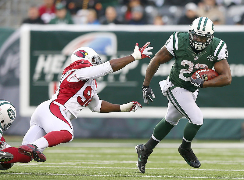 . Shonn Greene #23 of the New York Jets carries the ball as  Sam Acho #94 of the Arizona Cardinals defends on December 2, 2012 at MetLife Stadium in East Rutherford, New Jersey. The New York Jets defeated the Arizona Cardinals 7-6.(Photo by Elsa/Getty Images)