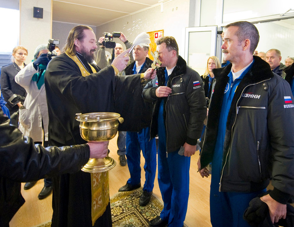 . An Orthodox priest blesses the International Space Station (ISS) crew members from left to right in blue overall., U.S. astronaut Thomas Marshburn, Russian cosmonaut Roman Romanenko and Canadian astronaut Chris Hadfield before they leave a hotel for a final pre-launch preparation at the Baikonur Cosmodrome, Wednesday, Dec. 19, 2012.  (AP Photo/Sergei Remezov, Pool)