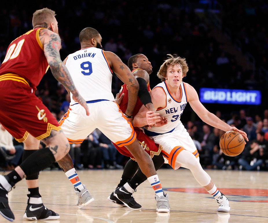. New York Knicks guard Ron Baker (31) drives around Cleveland Cavaliers guard Kay Felder, second from right, in the second half of an NBA basketball game at Madison Square Garden in New York, Wednesday, Dec. 7, 2016. The Cavaliers crushed the Knicks 126-94. New York Knicks center Kyle O\'Quinn (9) backs up Baker as Cleveland Cavaliers forward Chris Andersen, far left, defends. (AP Photo/Kathy Willens)