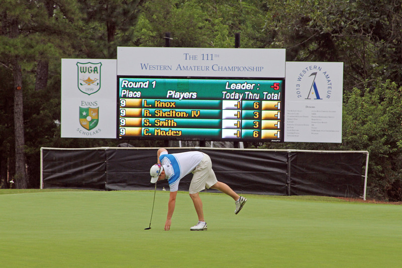 Geoff Drakeford of Yarram, Australia reaches into the 14th cup in front of one of the numerous electronic scoreboards located throughout The Alotain Club in Roland, AR at the 2013 Western Amateur. (WGA Photo/Ian Yelton)