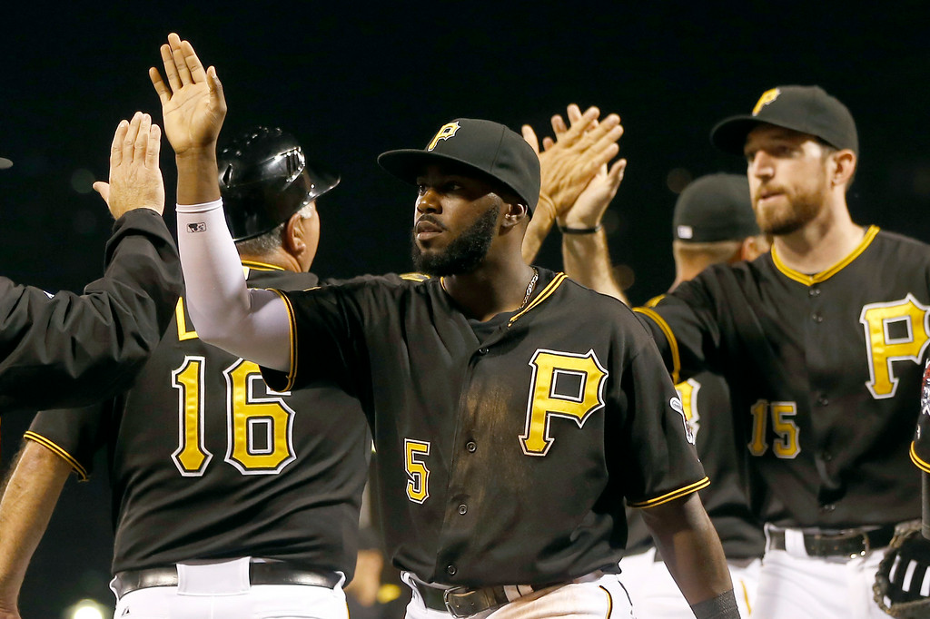 . Pittsburgh Pirates\' Josh Harrison (5) and Ike Davis celebrate with teammates after they defeated the Detroit Tigers in the baseball game on Tuesday, Aug. 12, 2014, in Pittsburgh. The Pirates won 4-2. (AP Photo/Keith Srakocic)