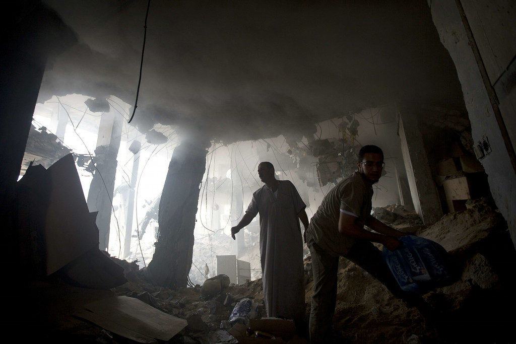 . Palestinian men remove goods from the rubble of a destroyed store located on the ground floor of a building hit by an Israeli air strike on July 22, 2014 in Gaza city. UN chief Ban Ki-moon and US Secretary of State John Kerry are in Cairo today in a bid to broker a truce between Israel and Hamas after two weeks of fighting which has left over 570 Palestinians dead. AFP PHOTO / MAHMUD HAMS/AFP/Getty Images