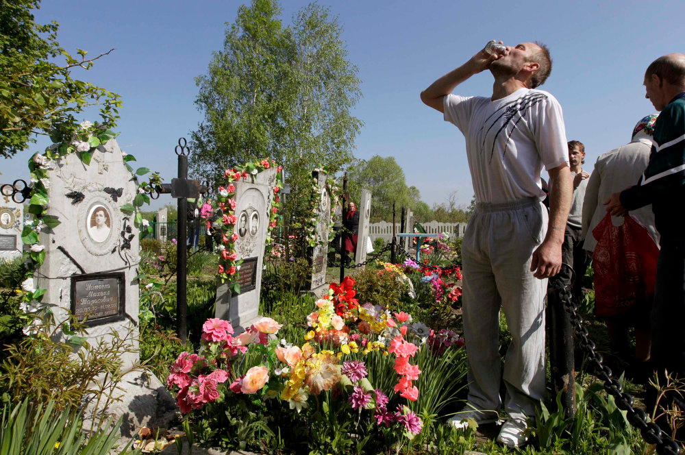 . A man drinks vodka at a grave during Orthodox Easter in the village of Pogost, some 250 km (155 miles) south of Minsk May 5, 2013. Villagers in southern parts of Belarus visit their relatives\' graves during Easter celebrations on Sunday.   REUTERS/Vasily Fedosenko