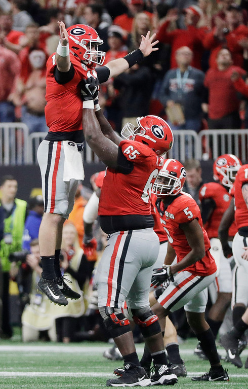 . Georgia\'s Kendall Baker lifts quarterback Jake Fromm (11) after a long touchdown pass during the second half of the NCAA college football playoff championship game against Alabama Monday, Jan. 8, 2018, in Atlanta. (AP Photo/David J. Phillip)