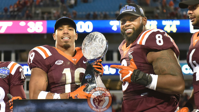 Virginia Tech defensive back Chuck Clark (19) and defensive tackle Nigel Williams (8) pose on stage with the Belk Bowl trophy. (Michael Shroyer/ TheKeyPlay.com)
