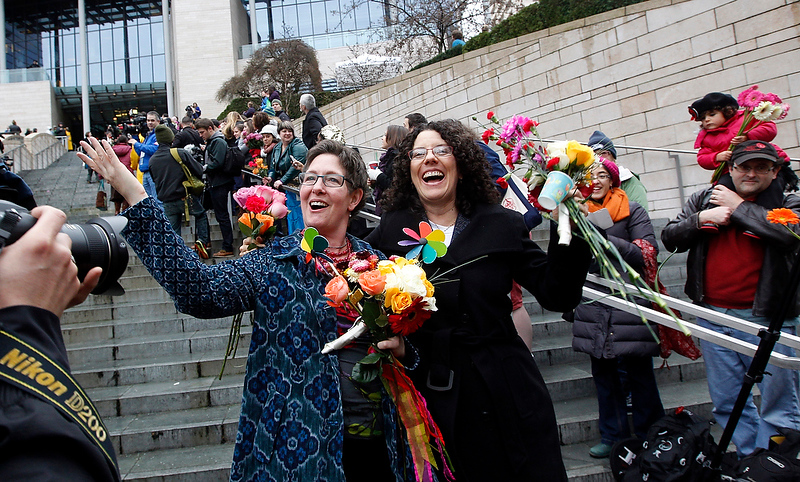 . Newlyweds Johanna Flynn, left, and Allison Kelsey wave back to well-wishers as they depart Seattle City Hall, Sunday, Dec. 9, 2012, in Seattle. (AP Photo/Elaine Thompson)