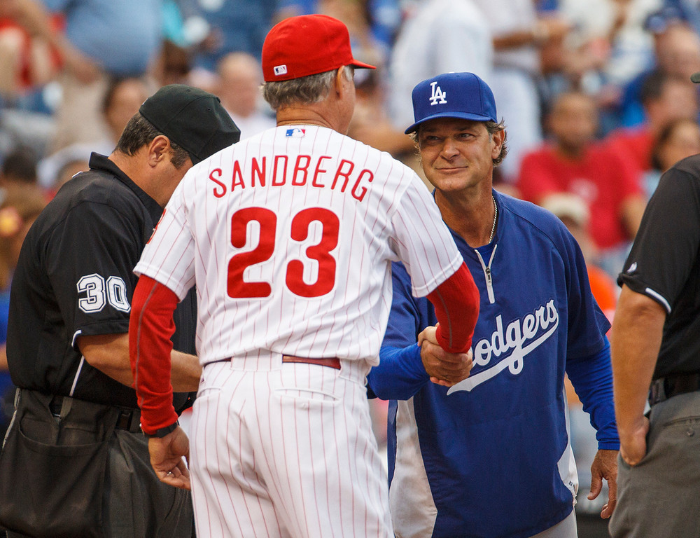 . Los Angeles Dodgers manager Don Mattingly, right, shakes hands with Philadelphia Phillies interim manager Ryne Sandberg as they hand in their line-up cards before  a baseball game on Friday, Aug. 16, 2013, in Philadelphia. (AP Photo/Christopher Szagola)