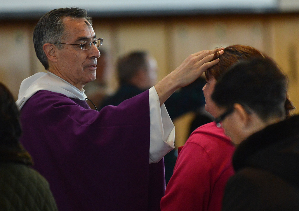 . Father Roberto Corral puts ashes on the forehead of a woman during Ash Wednesday mass  at Holy Rosary Church in Antioch, Calif., on Wednesday Sept. 13, 2013. (Dan Rosenstrauch/Staff)