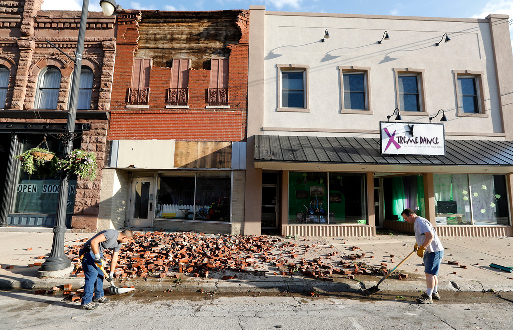 . Workers clean up bricks from a tornado-damaged business on Main Street, Thursday, July 19, 2018, in Marshalltown, Iowa. Several buildings were damaged by a tornado in the main business district in town including the historic courthouse. (AP Photo/Charlie Neibergall)