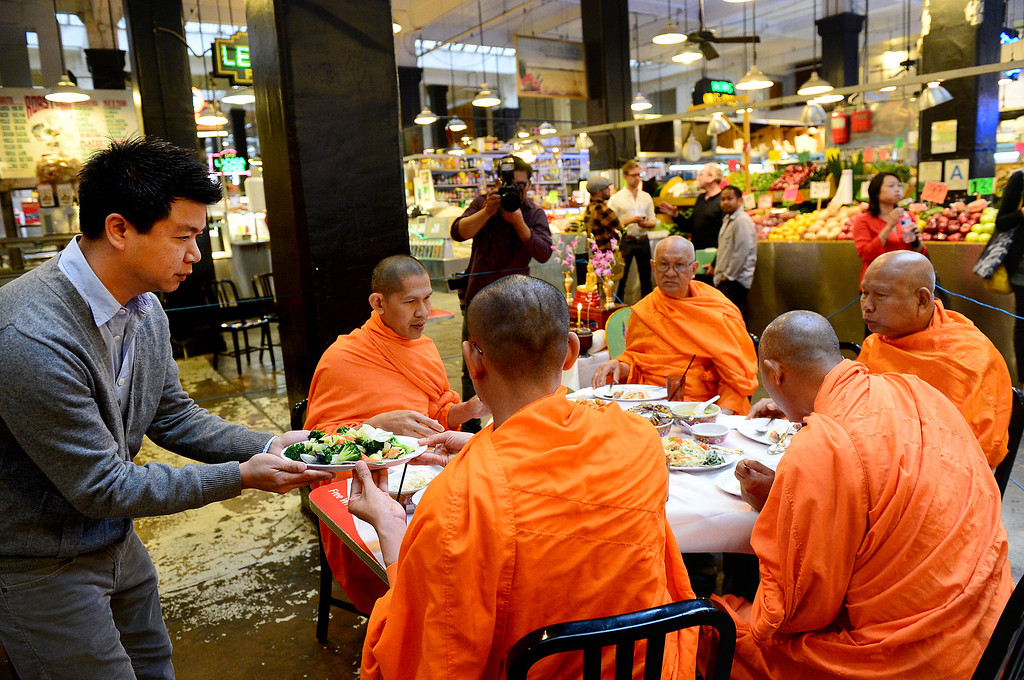 . David Tewasart, of Pasadena, serves Wat Thai Temple monks, of North Hollywood, lunch after they blessed the opening of his restaurant Sticky Rice at Grand Central Market in downtown Los Angeles Monday, April 30, 2013. (SGVN/Staff Photo by Sarah Reingewirtz)