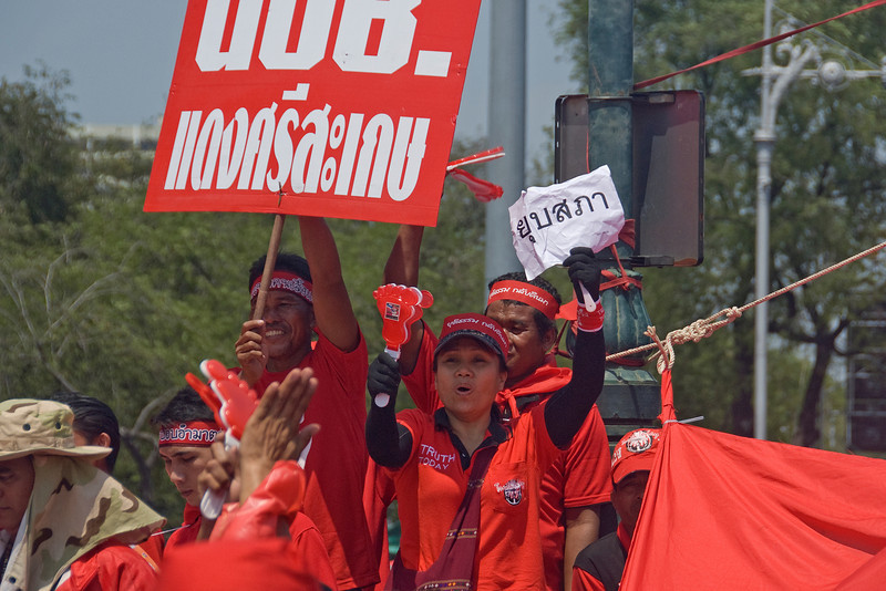 Protesters holding out signs during Red Shirt Protest in Thailand