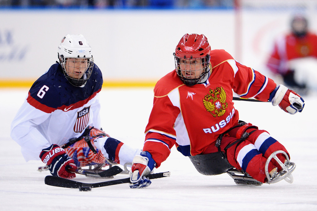 . Declan Farmer of the United States chases Konstantin Shikhov of Russia during the ice sledge hockey gold medal game between the Russian Federation and the United States of America at the Shayba Arena during day eight of the 2014 Paralympic Winter Games on March 15, 2014 in Sochi, Russia.  (Photo by Dennis Grombkowski/Getty Images)
