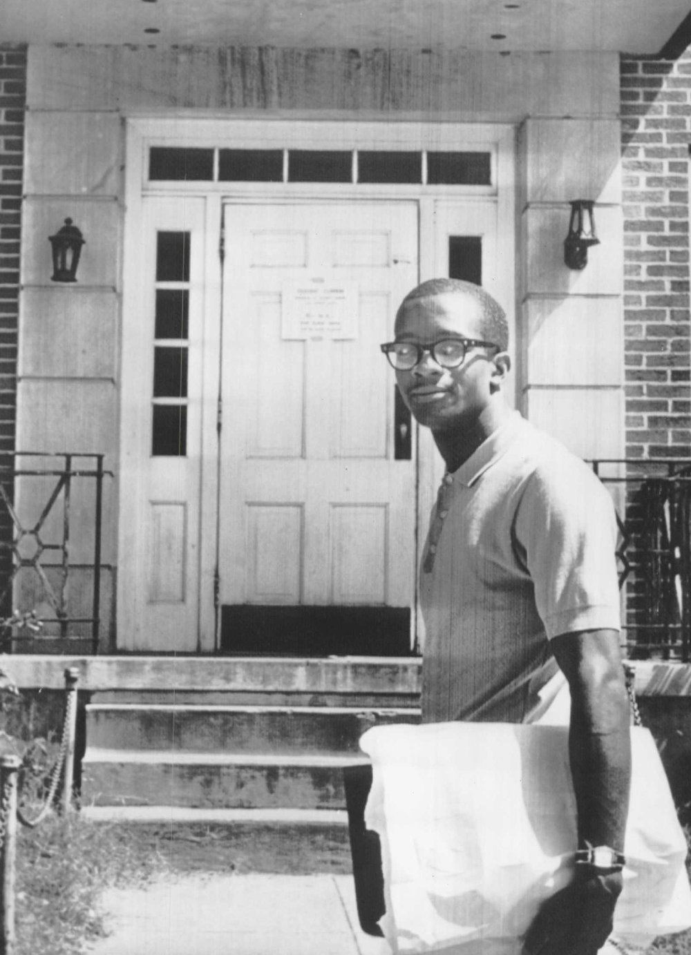 . James Hood poses at the doorway of Palmer Hall on the campus of the University of Alabama at Tuscaloosa as he returns to his residence hall after his first class today. He holds a bundle of books just purchased at the campus bookstore. A student curfew notice is tacked on the door. (The Denver Post Archive)