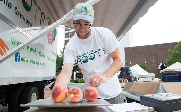 08/21/19 Wesley Bunnell | Staff Nic Tedesco weights a customers produce at the ROOTS mobile farmers market truck at Central Park on Wednesday afternoon August 21, 2019.