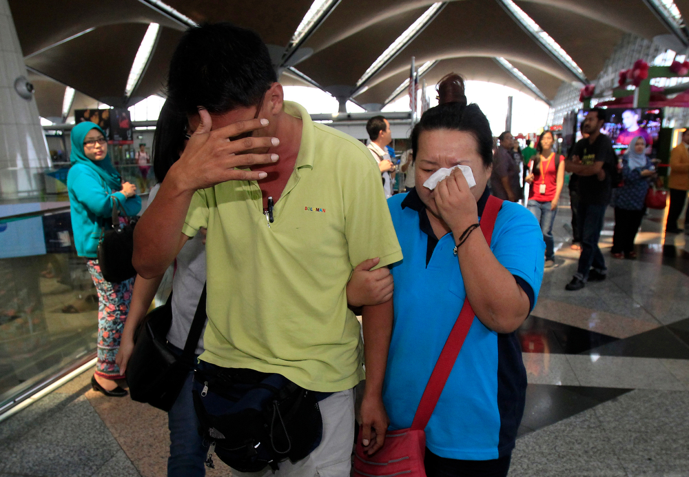 . A woman wipes her tears after walking out of the reception center and holding area for family and friend of passengers aboard a missing Malaysia Airlines plane, at Kuala Lumpur International Airport in Sepang, outside Kuala Lumpur, Malaysia, Saturday, March 8, 2014. Search teams across Southeast Asia scrambled on Saturday to find a Malaysia Airlines Boeing 777 with 239 people on board that disappeared from air traffic control screens over waters between Malaysia and Vietnam early that morning. (AP Photo/Lai Seng Sin)