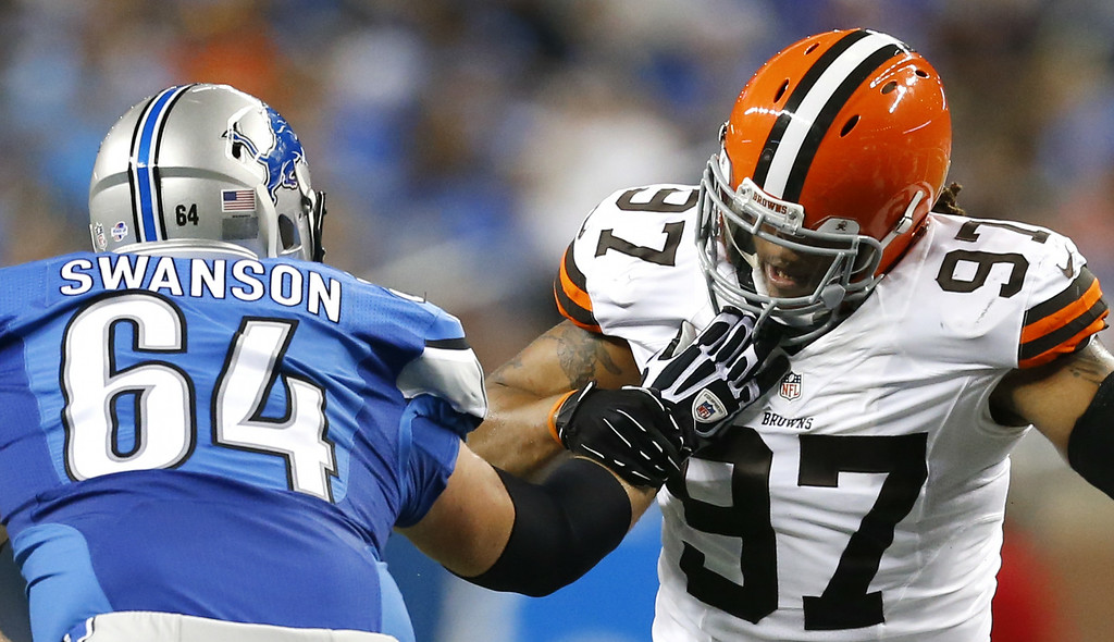 . Cleveland Browns outside linebacker Jabaal Sheard (97) fights off Detroit Lions center Travis Swanson (64) in the first half of a preseason NFL football game at Ford Field in Detroit, Saturday, Aug. 9, 2014.  (AP Photo/Rick Osentoski)