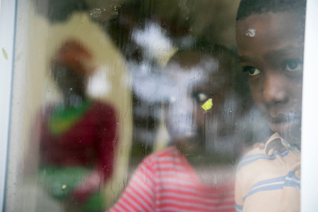 . Boys look out the window of the Hoyo de Friusa Community Center, which is serving as a shelter while Hurricane Maria approaches the coast of Bavaro, Dominican Republic, Wednesday, Sept. 20, 2017. The U.S. National Hurricane Center says Maria has lost its major hurricane status, after raking Puerto Rico. But forecasters say some strengthening is in the forecast and Maria could again become a major hurricane by Thursday. (AP Photo/Tatiana Fernandez)
