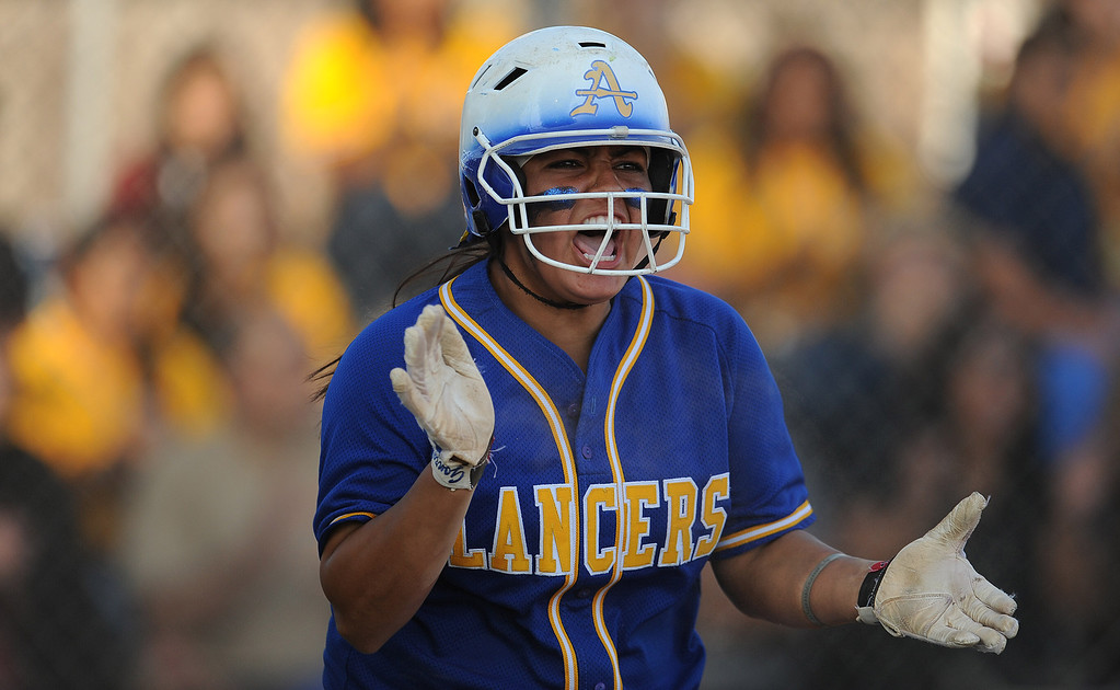 . Bishop Amat\'s Alexis Gonzalez (C) reacts after scoring on a bunt by Brandy Galaviz (C) (not pictured) to take a 5-3 lead in the sixth inning of a prep softball game against Santiago at Bishop Amat High School on Wednesday, March 27, 2013 in La Puente, Calif. Bishop Amat won 5-3.  (Keith Birmingham Pasadena Star-News)