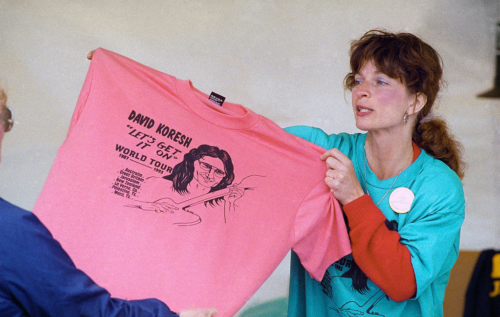 ". Linda Cox displays a T-shirt that she is selling near the Branch Davidian compound near Waco, Texas on March 18, 1993. The shirt says ""David Koresh left\'s get it on world tour.\"" (AP Photo/Rich Bowmer)"