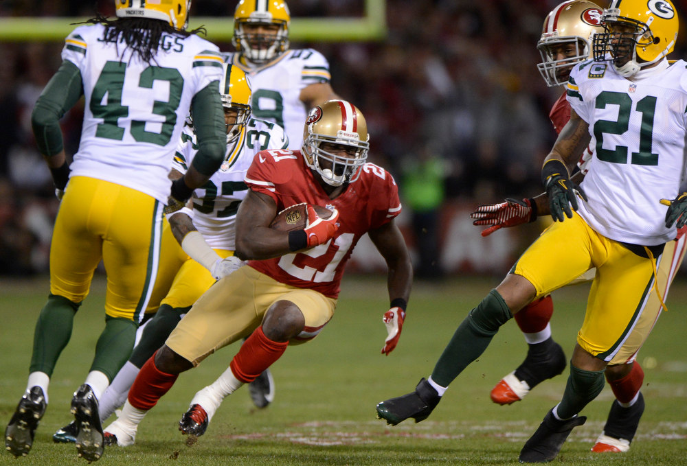 Description of . San Francisco 49ers running back Frank Gore (21) weaves through Green Bay Packers defenders with a 45-yard pass reception in the first quarter in the NFC Divisional Playoff on Saturday, January 12, 2013, at Candlestick Park in San Francisco, California. (Jose Carlos Fajardo/San Jose Mercury News)