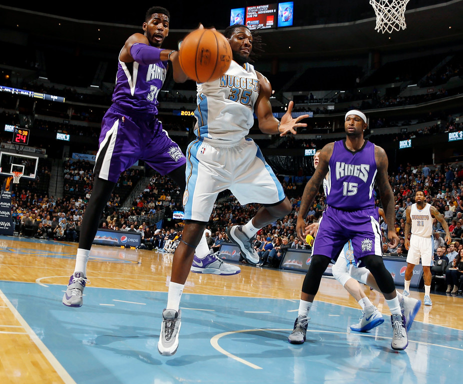 . Sacramento Kings forward Jason Thompson, left, knocks the ball away from Denver Nuggets forward Kenneth Faried as Kings center DeMarcus Cousins, right, looks on in the first quarter of an NBA basketball game in Denver on Monday, Nov. 3, 2014. (AP Photo/David Zalubowski)