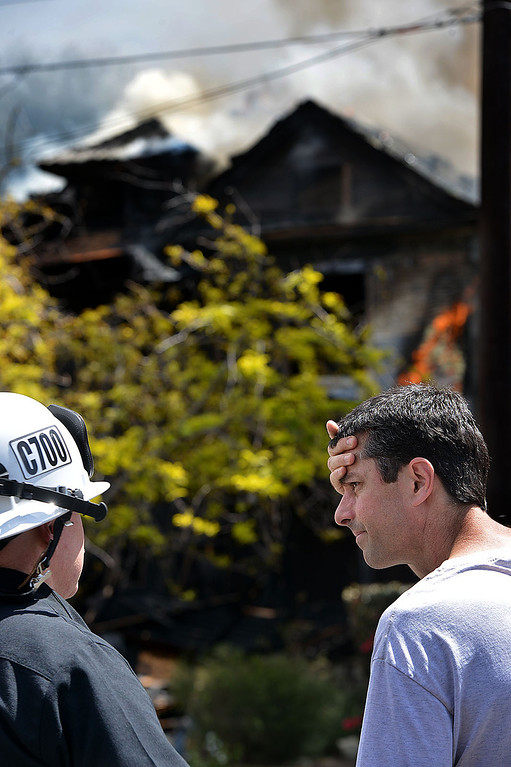 . Tim McNaughton, right, speaks with Jeff Frazier, Chief of the Redlands Fire Department, as firefighters work to extinguish a fire burning McNaughton\'s home. The home in the 1600 block of Olive Street, one of the city�s historic neighborhoods, was destroyed in a fire Wednesday April 9, 2014, according to fire officials. As they arrived, firefighters found the home, built in 1903, engulfed in flames and smoke billowing out of the structure. (Photo by Rick Sforza/The Sun)