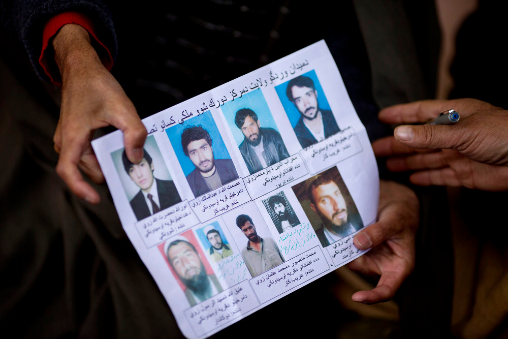 . Afghan villagers show a paper with pictures of relatives held in U.S. Special Forces custody in Maidan Shahr, Wardak province, Afghanistan, Sunday, March 10, 2013. Afghan President Hamid Karzai, infuriated by villager reports of forced detentions and mass arrests, gave U.S. Special Forces two weeks to vacate Wardak province, located barely 30 kilometers (24 miles) from the Afghan capital of Kabul. The deadline for their withdrawal expired midnight Sunday, March 10, 2013. (AP Photo/Anja Niedringhaus)