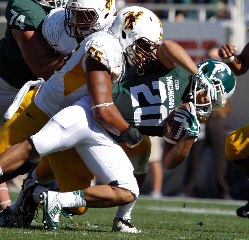 . Wyoming\'s Eddie Yarbrough (55) takes down Michigan State\'s Nick Hill (20) during the first quarter of an NCAA college football game, Saturday, Sept. 27, 2014, in East Lansing, Mich. Michigan State won 56-14. (AP Photo/Al Goldis)
