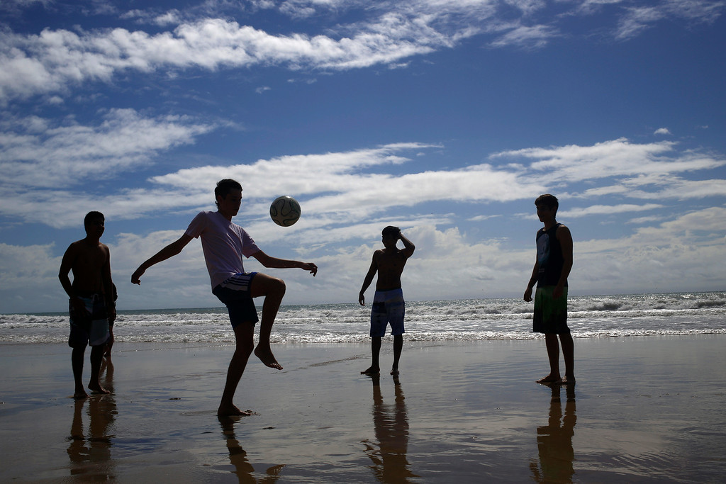 . Residents and tourists play soccer on Ponta Negra beach in Natal, Brazil, Wednesday, June 25, 2014. Natal is one of many cities hosting the World Cup soccer tournament this month. (AP Photo/Hassan Ammar)