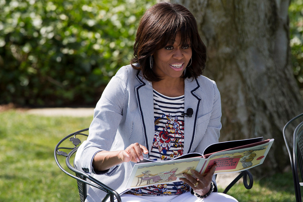 ". First lady Michelle Obama reads the book ""Cloudy With A Chance of Meatballs\"" to children as part of the annual White House Easter Egg Roll, Monday, April 1, 2013 on the South Lawn of the White House in Washington. (AP Photo/Jacquelyn Martin)"