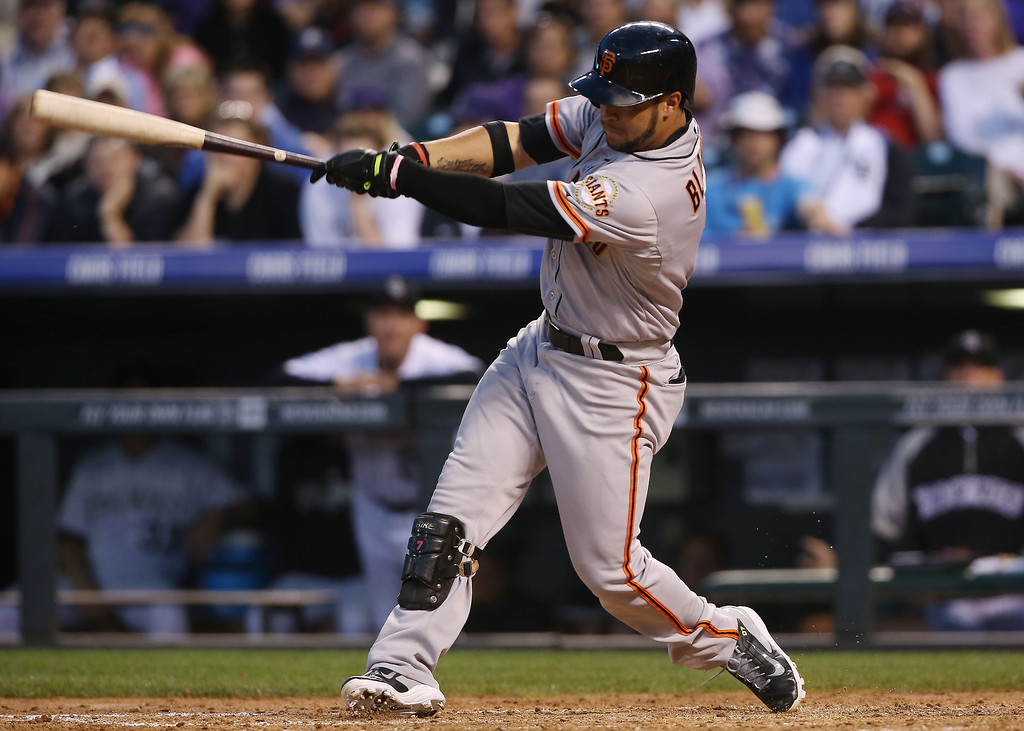 . San Francisco Giants\' Gregor Blanco follows through with his swing after connecting for a triple to drive in two runs against the Colorado Rockies in the fifth inning of a baseball game in Denver on Tuesday, May 20, 2014. (AP Photo/David Zalubowski)