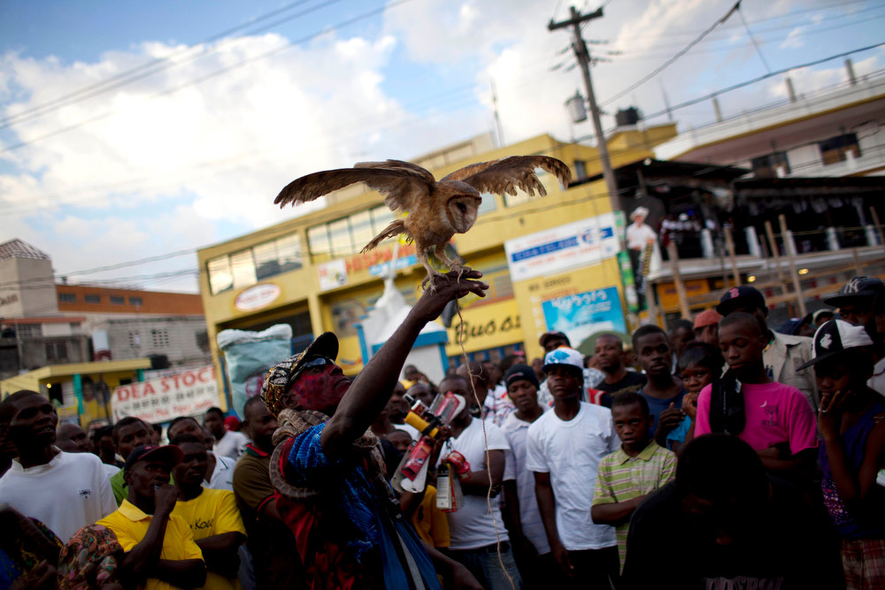Description of . In this Jan. 27, 2013 photo, snake handler Saintilus Resilus performs with an owl he caught in the wild just days before as he performs during pre-Lenten Carnival season  in Petionville, Haiti. This year, Resilus has new catches to display: an owl that he promises to let them go after Carnival.  (AP Photo/Dieu Nalio Chery)