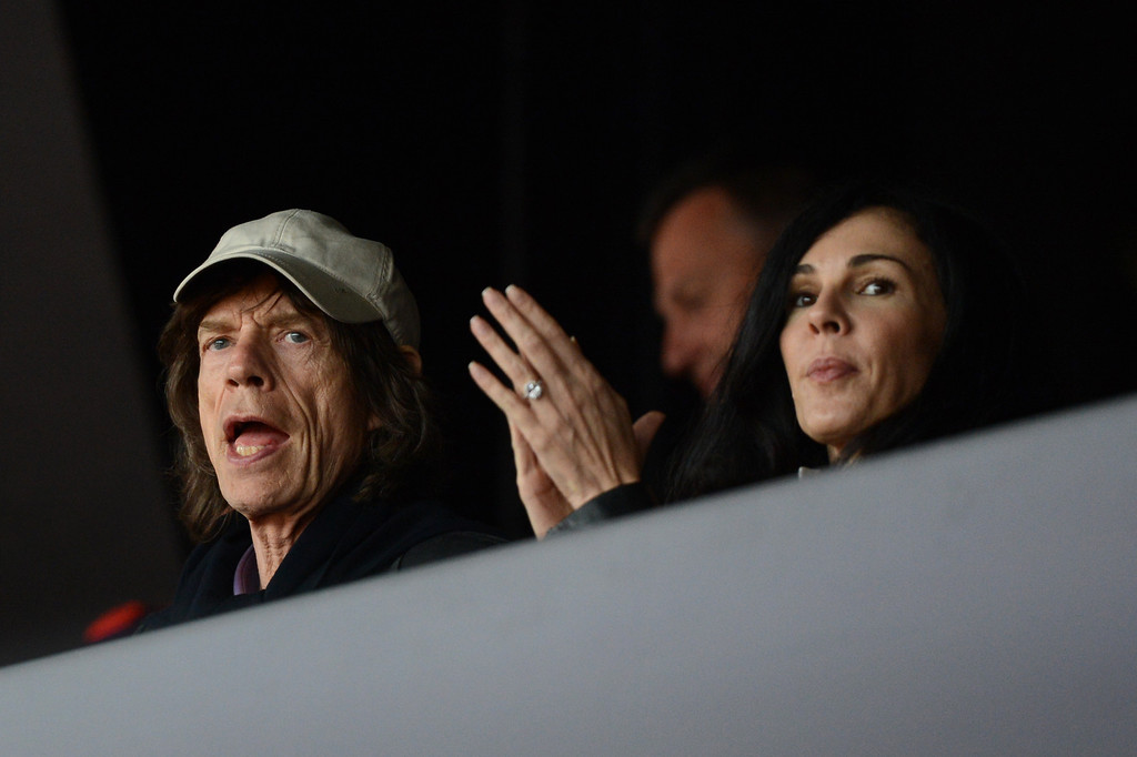 . British musician Mick Jagger\'s and his partner, US fashion designer L\'wren scott, attend the athletics event held at the Olympic Stadium during the London 2012 Olympic Games on August 6, 2012 in London. AFP PHOTO / JOHANNES EISELE        (Photo credit should read JOHANNES EISELE/AFP/GettyImages)