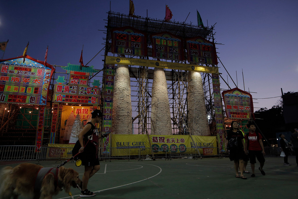 . People walk in front of the bun towers on the outlying Cheung Chau island in Hong Kong, Tuesday, May 22, 2018 to celebrate the Bun Festival. During the Bun Festival, the Taoist God of the Sea, is worshipped and evil spirits are scared away by loud gongs and drums during the procession. The celebration includes bun scrambling, parades, opera performances, and children dressed in colorful costumes. (AP Photo/Kin Cheung)
