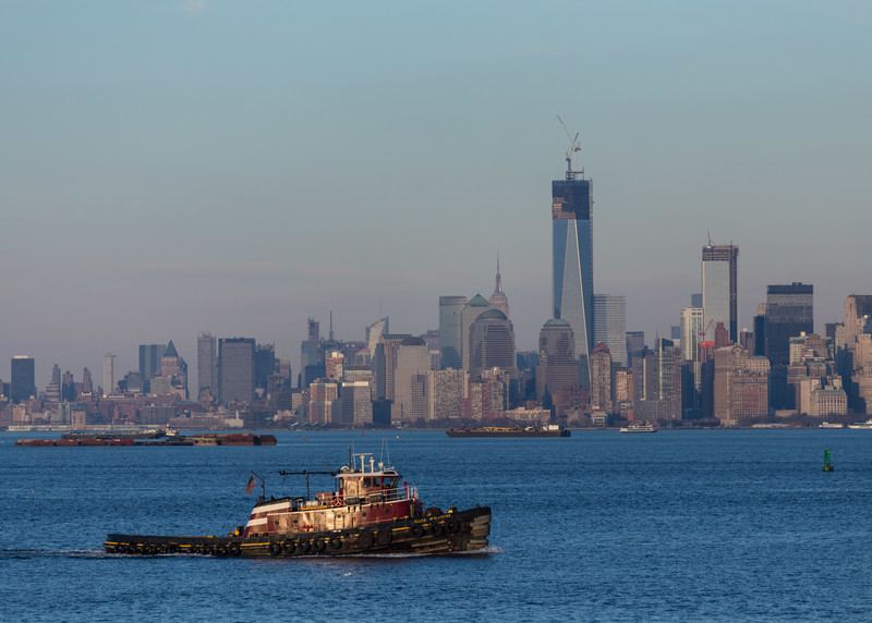 Downtown New York City, including One World Trade Center, as viewed from the Staten Island Ferry; tugboat in the foreground.