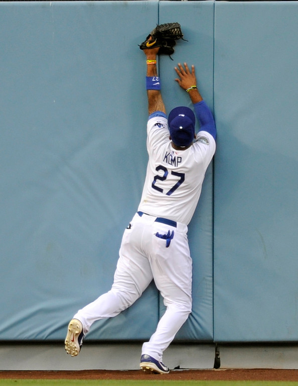 . Dodgers center fielder Matt Kemp crashes against the outfield wall while making a catch on a deep fly by the Cubs Alfosnso Soriano in the first inning, Friday, August 3, 2012, at Dodger Stadium. (Michael Owen Baker/Staff Photographer)