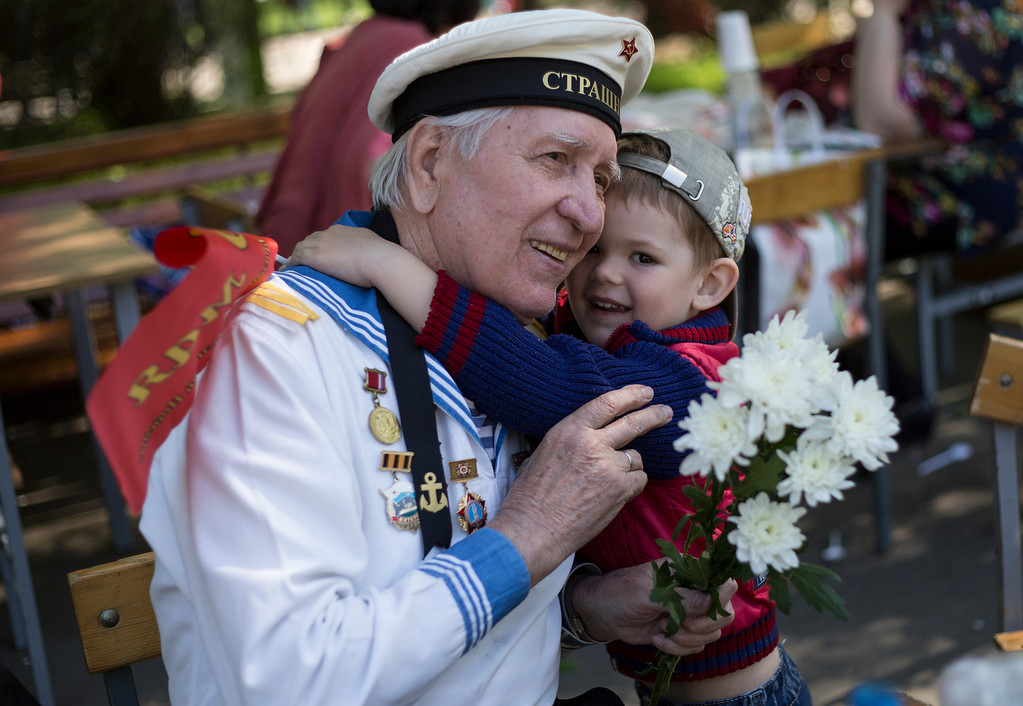 . Russian WWII veteran Viktor Shepelev, 86, hugs a young boy as he receive flowers from him during a celebration of Victory day in Moscow\'s Gorky park, Russia, Friday, May 9, 2014. (AP Photo/Denis Tyrin)