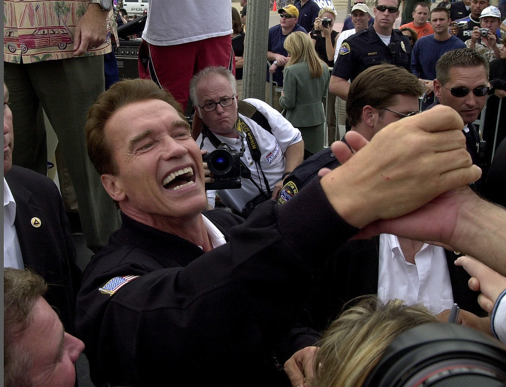 . 10/6/03 - Arnold Schwarzenegger candidate for California Governer shakes hands with supporters at the Hungtington Beach Pier, a ralley the day before the recall election.