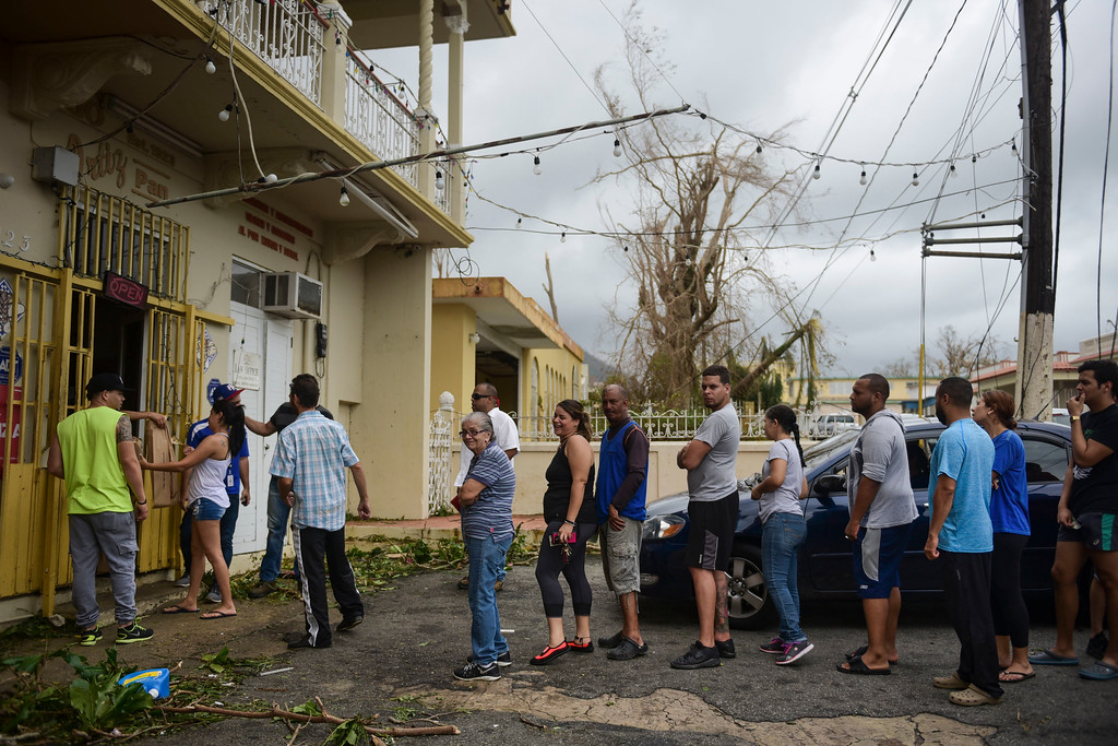 . People wait in line to buy bread at Ortiz bakery after the passing of Hurricane Maria, in Yabucoa, Puerto Rico, Thursday, September 21, 2017. As of Thursday evening, Maria was moving off the northern coast of the Dominican Republic with winds of 120 mph (195 kph). The storm was expected to approach the Turks and Caicos Islands and the Bahamas late Thursday and early Friday. (AP Photo/Carlos Giusti)